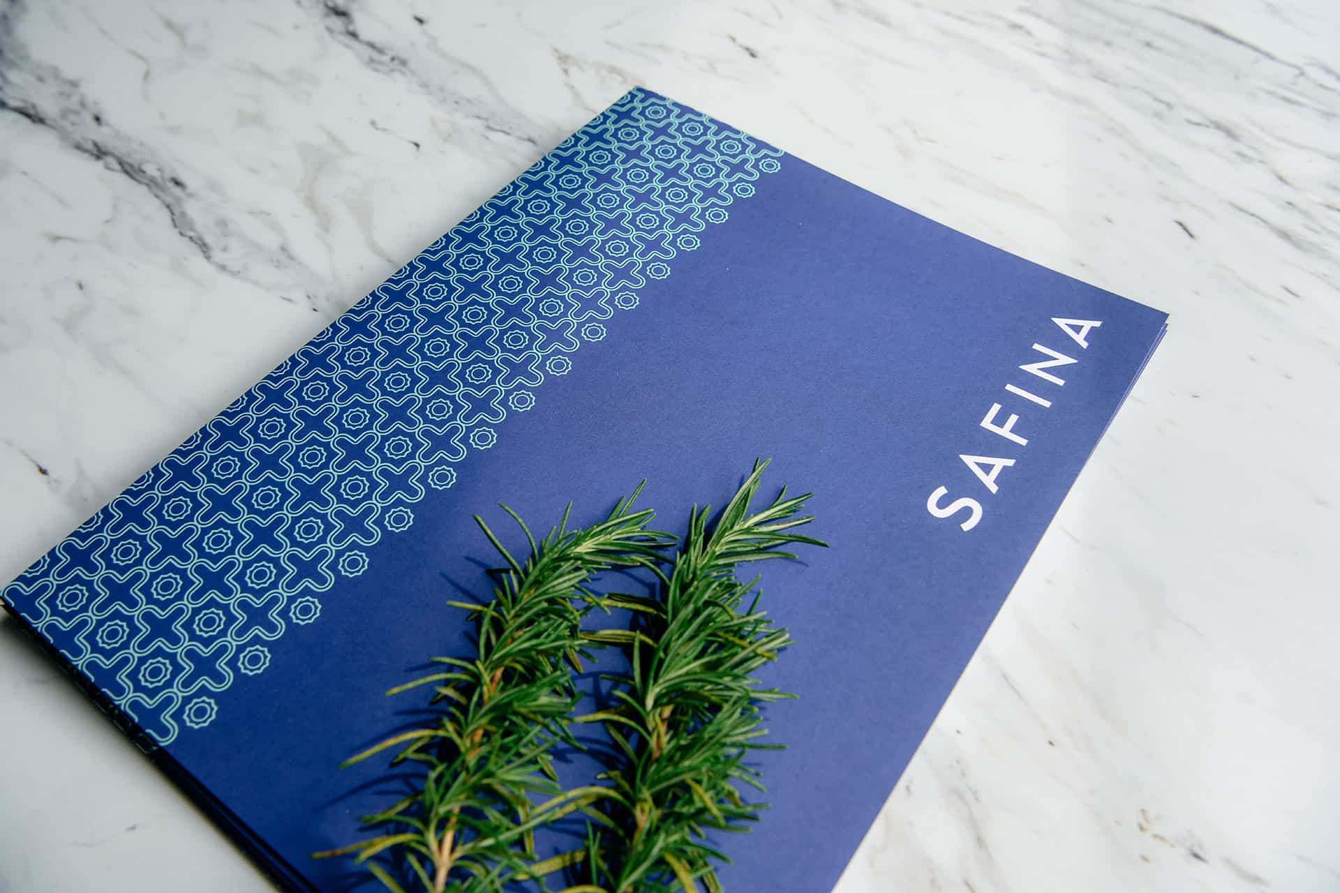 Safina's multiple brand touch points took inspiration from the Mediterranean in color and craft. Faux leather featured the brand's colors in all their vibrancy creating a calming and uplifting experience. The full suite of menus equipped the brand with many options for their different day parts and dining experience needs. Additional character-driven pieces were designed to add special notes to the experience. Coasters through matchboxes served as final touches to a complete brand identity menu design